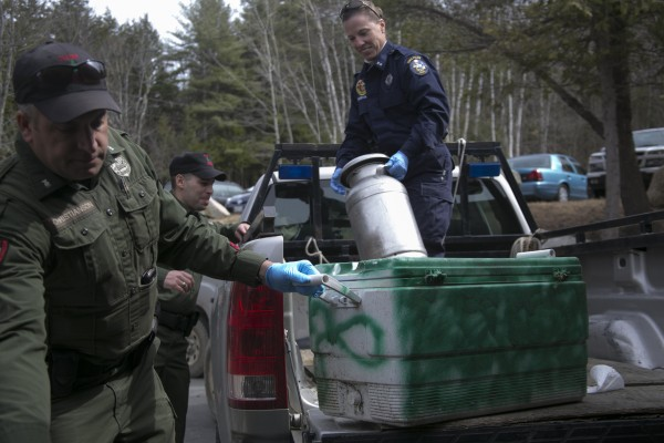 Maine State Trooper Diane Perkins-Vance unloads evidence with Maine game warden officer at the Pine Tree Camp in Rome taken from Christopher  Knights campsite near North Pond. Items collected included cookware, propane tanks, ATV batteries and handheld videogames.