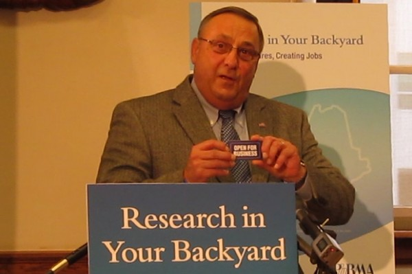 Gov. Paul LePage holds up one of his business cards, which says &quotOpen for Business&quot on the back, before giving it to John Castellani, CEO of the Pharmaceutical Research and Manufacturers of America, during a press conference at the State House on April 19, 2013.