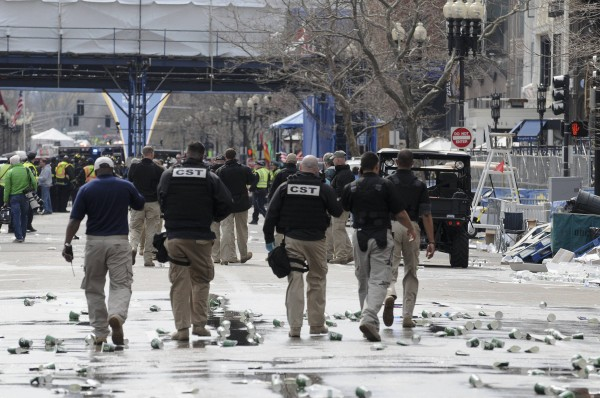 Public safety officials evacuate the scene after two explosions near the finish line of the 117th Boston Marathon in Boston, Mass., on Monday.
