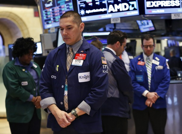Traders on the floor at the New York Stock Exchange join the moment of silence in honor of the Boston marathon victims, April 22, 2013.