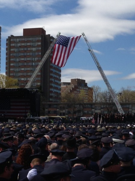 A flag hangs during the memorial service at Massachusetts Institute of Technology for MIT police officer Sean Collier.