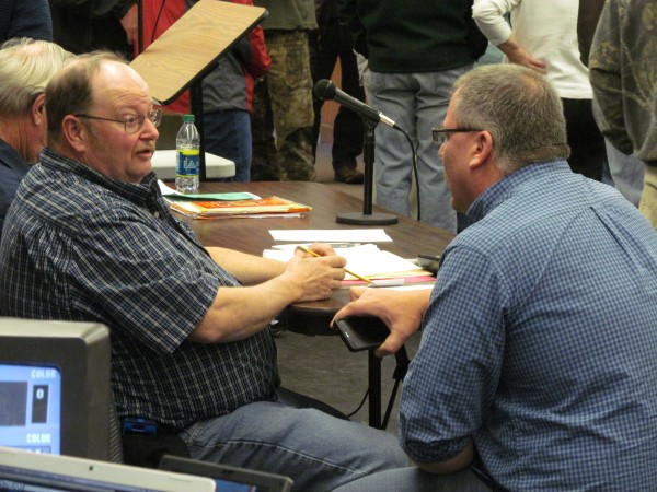 Baldwin selectman Jeffrey Sanborn talks with a constituent while residents take a paper-ballot vote on who would moderate a special town meeting Saturday. The meeting was held because some in the town wanted to overturn changes to selectmen pay made at the annual town meeting last month.