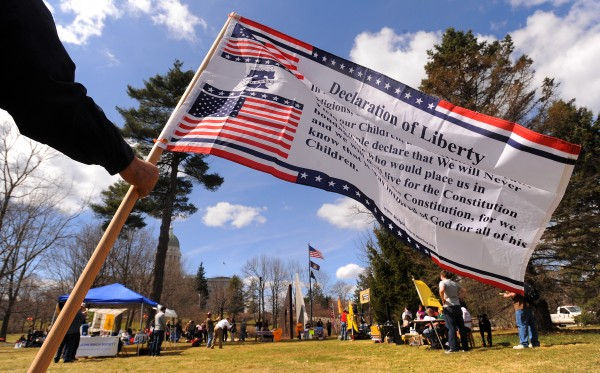 Dana Lagassie of Vassalboro flies a Declaration of Liberty flag during a Patriots Day rally at Capitol Park in Augusta on Monday.
