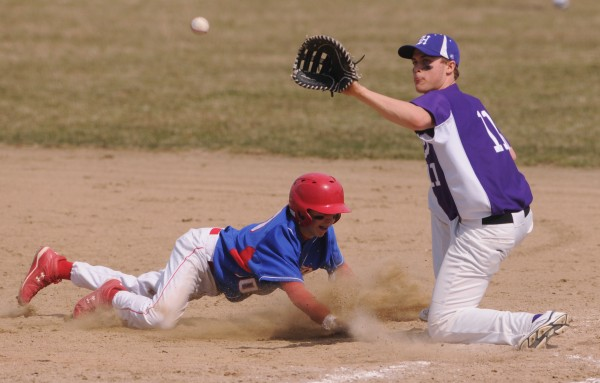Messalonskee runner Jared Cunningham dives back to first base as Hampden's Sam Ward takes a throw from Hampden's catcher, Pat Later, during 6th inning action at Hampden.