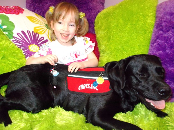 Faith McNally, 5, the adopted daughter of Bruce and Beverly McNally of Island Falls, suffers from spina bifida and life-threatening seizures. She poses here with her black Labrador retriever, Dandy, who serves as an assistance dog to help her cope with her seizures.