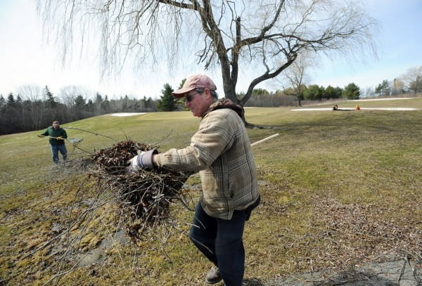 Robert Waugh and Robert Irwin (background), grounds crew, rake up sticks at Bangor Municipal Golf Course on Thursday in preparation for the start of the season.