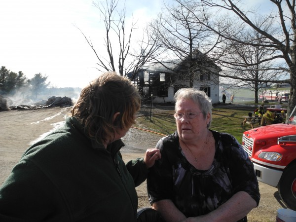 Jackie Bryant is comforted by a friend Monday afternoon while her home burns behind her. &quotI feel like I'm too old to start over,&quot she said.