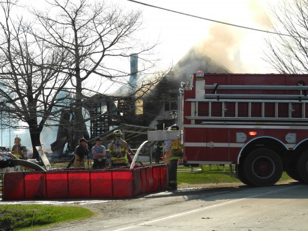 Firefighters from eight responding departments get more water to fight a fire Monday afternoon that consumed a house built in the 1800s on Route 137 in Knox. High winds drove sparks across the road, where a grass fire began but was extinguished shortly afterwards.