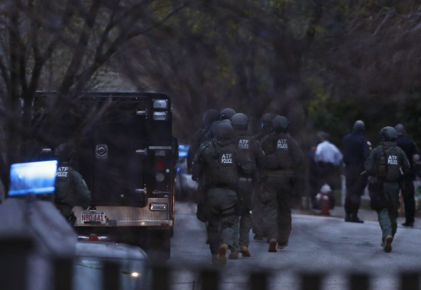 Police run down Franklin Street in Watertown, Massachusetts April 19, 2013. The surviving suspect in the Boston Marathon bombings was surrounded by police on Friday in Watertown, local media reported.