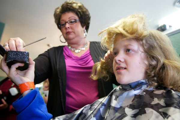 Stylist Amy Fabus divides Josh Demers' hair into pony tails before cutting it off for Locks of Love, an organization that makes wigs for cancer patients. Demers was originally growing his hair in hopes of giving it to a family friend, Angela Black, but she died of cancer just before her 40th birthday in 2012.