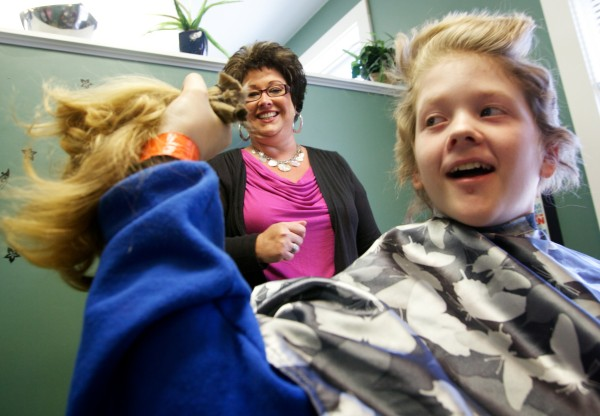 Josh Demers, 12, shows off his hair after stylist Amy Fabus cut it off for Locks of Love, an organization that makes wigs for cancer patients.