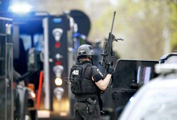 A police SWAT team member readies his weapon as he stands in the middle of Franklin Street as gunfire erupts on Franklin during the search for Dzhokhar Tsarnaev, the surviving suspect in the Boston Marathon bombings, in Watertown, Massachusetts April 19, 2013.