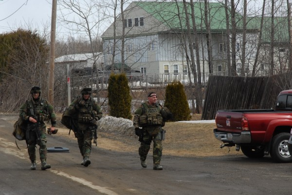 Members of a Maine State Police tactical unit walk back to their vehicles following the peaceful conclusion of 