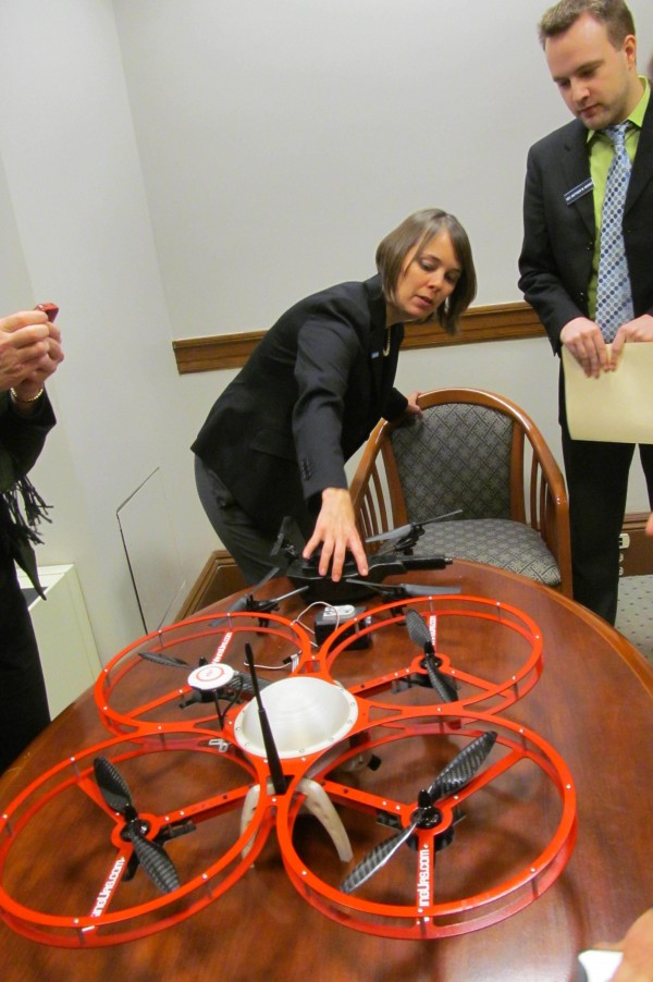 Shenna Bellows, executive director of the American Civil Liberties Union of Maine, (left) describes how various models of airborne surveillance drones work on Tuesday, Feb. 26, 2013, at the State House in Augusta. Looking on is Rep. Matthew Moonen, D-Portland.