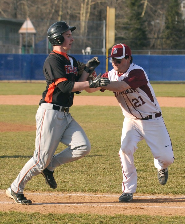 Bangor's Greg Duff (right) tags Skowhegan's Adam Clukey as he was running to first base during the game in Bangor on Monday.