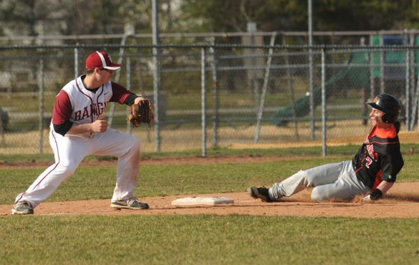 Skowhegan's Henry Ametti slides to third base, beating the tag by Bangor's Bryan Rouleau, during the game in Bangor on Monday.