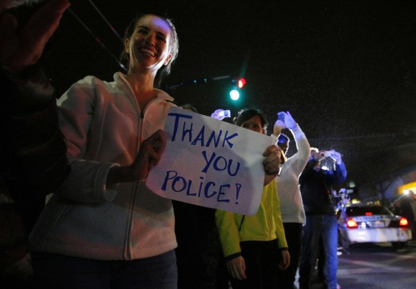 Members of the public cheer as police officers leave the scene where Dzhokhar Tsarnaev, the surviving suspect in the Boston Marathon bombings, was taken into custody in Watertown, Mass., on Friday night.