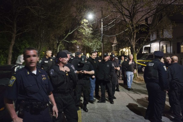 Law enforcement officials stand in front of 67 Franklin St. after the capture of Dzhokhar Tsarnaev, the surviving suspect in the Boston Marathon bombings, in Watertown, Mass., April 19, 2013.