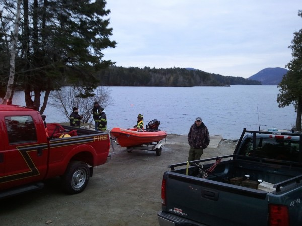 Response personnel stand by a boat ramp at the north end of Long Pond on Mount Desert Island as darkness falls Thursday evening. Searchers found a body and were searching for another one.