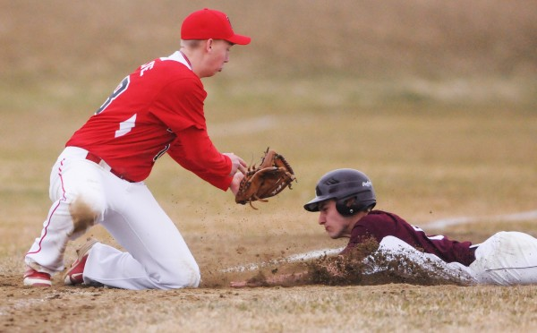 Foxcroft Academy's Cameron Fadley slides into third as Dexter's Matt Crane attempts to tag him out during fifth inning action at Dover Foxcroft on Thursday. Fadley was ruled safe.