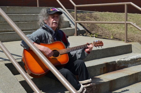 John White of Athens plays Bob Dylan songs on his  acoustic guitar as a small group protests marijuana laws across the street in front of the Somerset County Superior Court in Skowhegan on Monday.