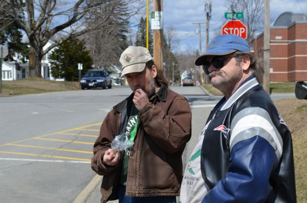 Donald Christen (left) eats a marijuana filled cookie as a Skowhegan police cruiser sits across High Street outside Somerset County Superior Court in Skowhegan on Monday. Charles Hutchins of Canaan (right) joined Christen as he protested marijuana laws for the 23rd consecutive year outside the courthouse.