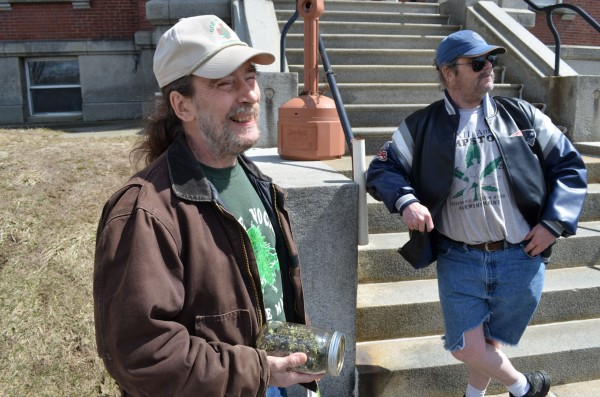 Donald Christen (left) holds a jar full of medical marijuana as he protests marijuana laws for the 23rd straight year outside Somerset County Superior Court in Skowhegan on Monday. Charles Hutchins of Canaan (right) also protested outside the courthouse.