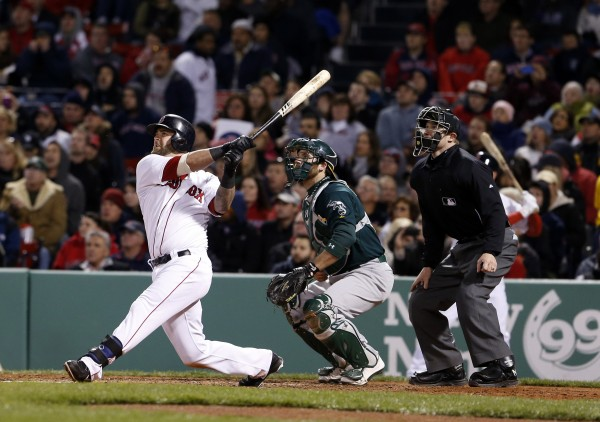 Boston Red Sox first baseman Mike Napoli (12) hits a grand slam home run in the fifth inning against the Oakland Athletics at Fenway Park on Monday.