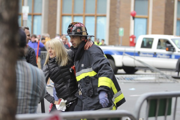An injured woman is attended to at the scene of an explosion at the Boston Marathon in Boston, Mass., on Monday. Two explosions struck the marathon as runners crossed the finish line on Monday, witnesses said, injuring more than 100 people on what is ordinarily a festive day in the city.
