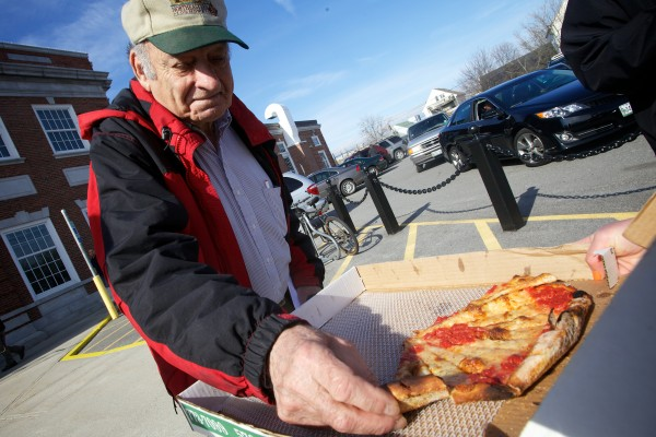 Richard Slosburg of Portland reaches for a slice of pizza handed out on tax day by the Maine People's Alliance outside the post office on Forest Avenue Monday. The small slices of pie are meant to represent the small amounts of tax they say are paid by corporations.