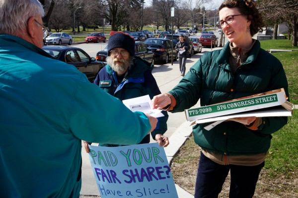 Amelia Mitter-Burke and Jim Devine of the Maine People's Alliance hand out fliers on tax day outside the post office on Forest Avenue in Portland.