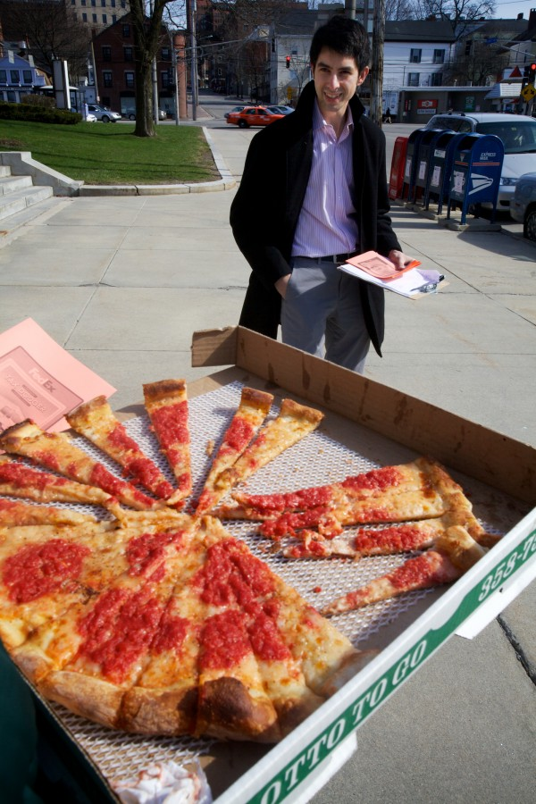 Maine People's Alliance organizer Kevin Simowitz and his colleagues hand out tiny slices of pizza outside th post office on Forest Avenue in Portland Monday.
