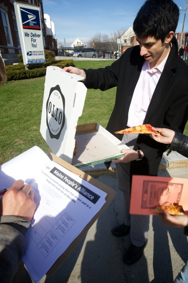 Maine People's Alliance organizer Kevin Simowitz and his colleagues hand out tiny slices of pizza outside the post office on Forest Avenue in Portland Monday.