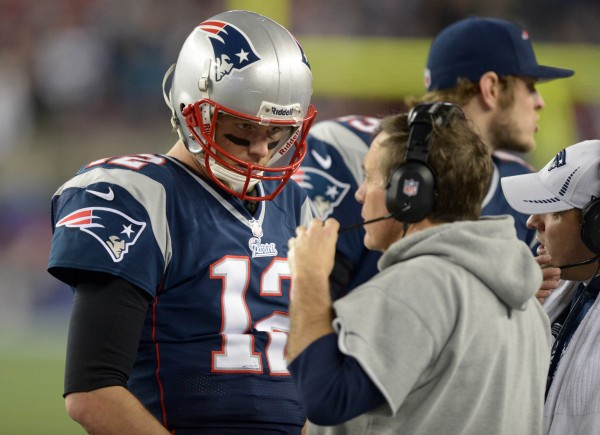 New England Patriots quarterback Tom Brady (12) listens to coach Bill Belichick (center) and offensive coordinator Josh McDaniels (right) during the AFC Divisional Round playoff game against the Houston Texans  in the AFC Divisional Round playoff game at Gillette Stadium in January.