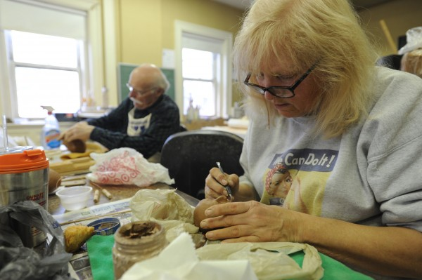 Pat Wyman works on sculpting a face in a pottery class at the Hammond Street Senior Center, where she is a member.  In background is Al Banfield, a new member of the center.