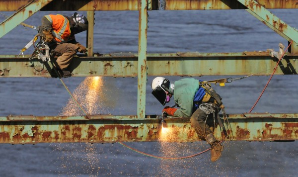 Workers use cutting torches to sever a section of the Waldo-Hancock Bridge before it is lowered by a crane to the deck of a waiting barge to be taken to Verona Island, where it will be cut up more and recycled.