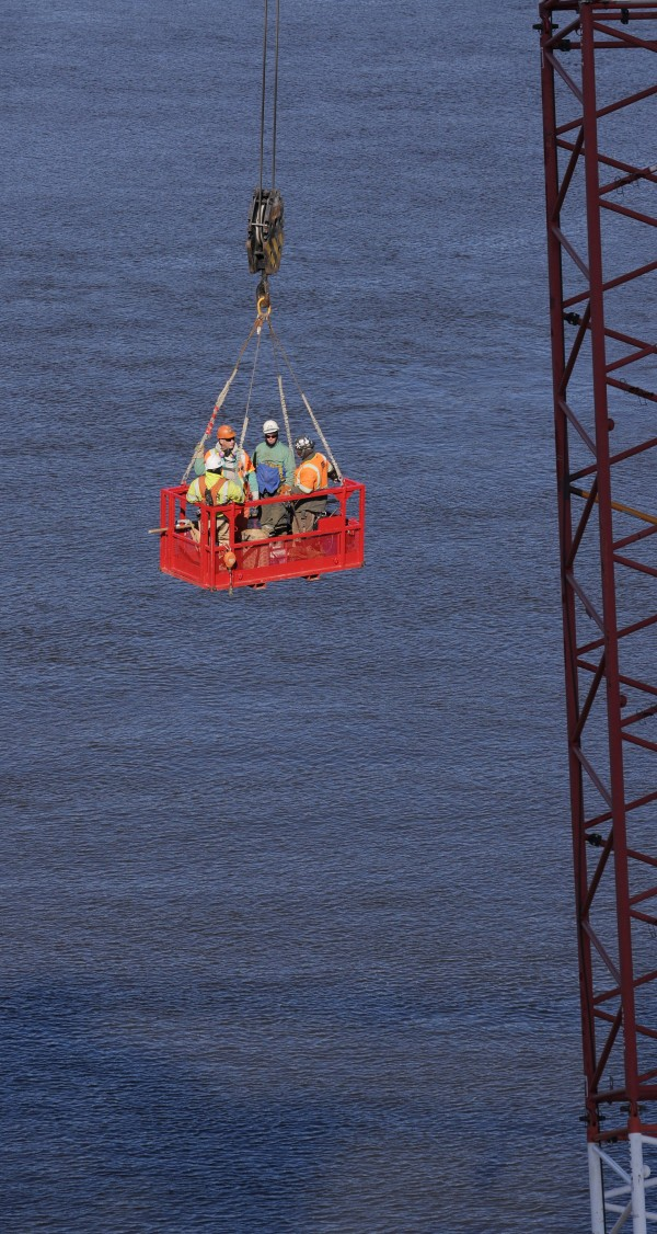 Workers ride in a basket after spending the day severing sections of the Waldo-Hancock Bridge.