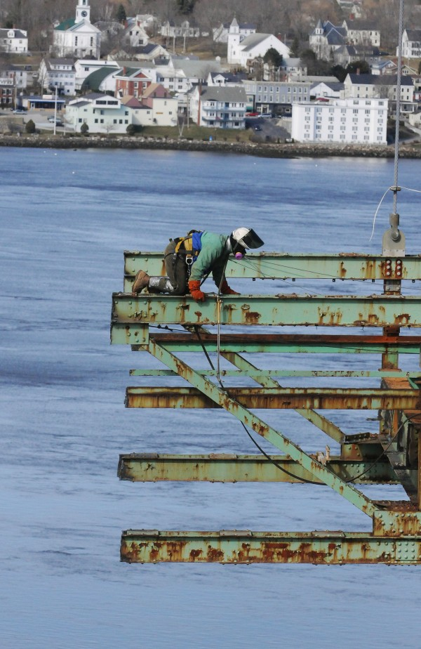 A worker crawls back to his crew after watching a steel section of the Waldo-Hancock Bridge be lowered by a crane to the deck of a waiting barge as it floats on the Penobscot River.