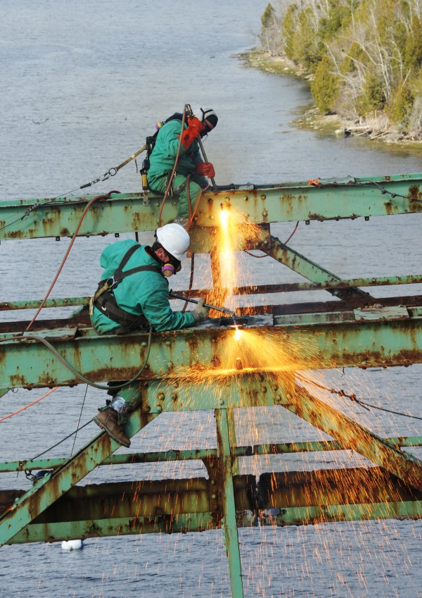 Workers use cutting torches to dismantle the Waldo-Hancock Bridge. Small sections are being cut out and lowered by a crane.