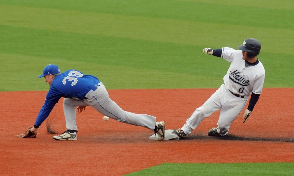 The University of Maine's Eric White (right) was safe at second base as Colby College's Benjamin Cocker could not make the catch.  White went on to score on the play during the second inning of the game in Orono Tuesday.