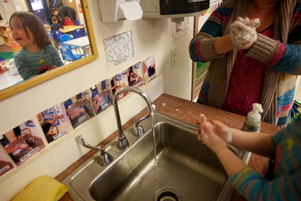 Emily learns to wash her hands with her teacher Shenna Otis after handling worms at the Head Start program in Bath Tuesday.