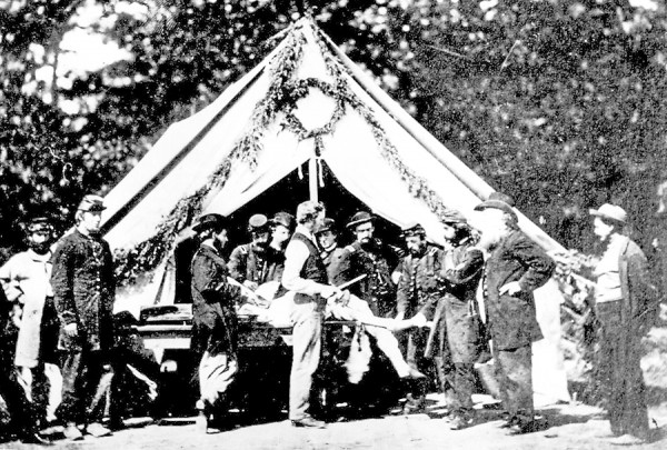 Medical personnel and other soldiers watch as an Army surgeon prepares to perform an amputation at Gettysburg field hospital in July 1863. During the Battle of Chancellorsville two months earlier, the two surgeons assigned to the 5th Maine Infantry Regiment worked at a similar hospital set up in Fredericksburg, Va. Heavy casualties kept the doctors busy.