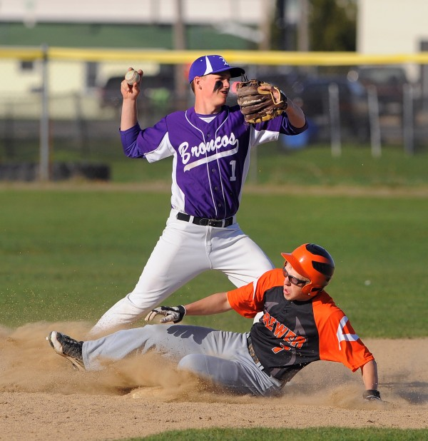 Hampden's Michael Ward throws the ball to fist base after forcing out Brewer's Matt Morrow at second base during the game in Brewer Monday. Hampden won the game 6-3.
