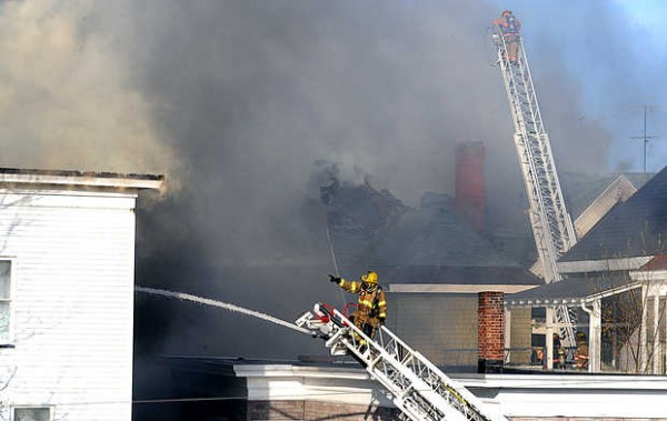 A firefighter points out a new batch of flames as multiple departments worked on squelching at least four apartment buildings located on Blake, Bates, and Pine Streets Monday.