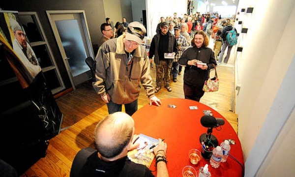 A long line of fans stretches behind Rocky Thompson and his fiancee, Rebecca Smullen, both of Conway, N.H., as they get an autograph from survival expert and musician Les Stroud on Thursday at Prose Gallery in Lewiston during the kickoff to the Lewiston Auburn Film Festival. Stroud's television show, &quotSurvivorman,&quot is aired on the Science and Discovery cable channels.