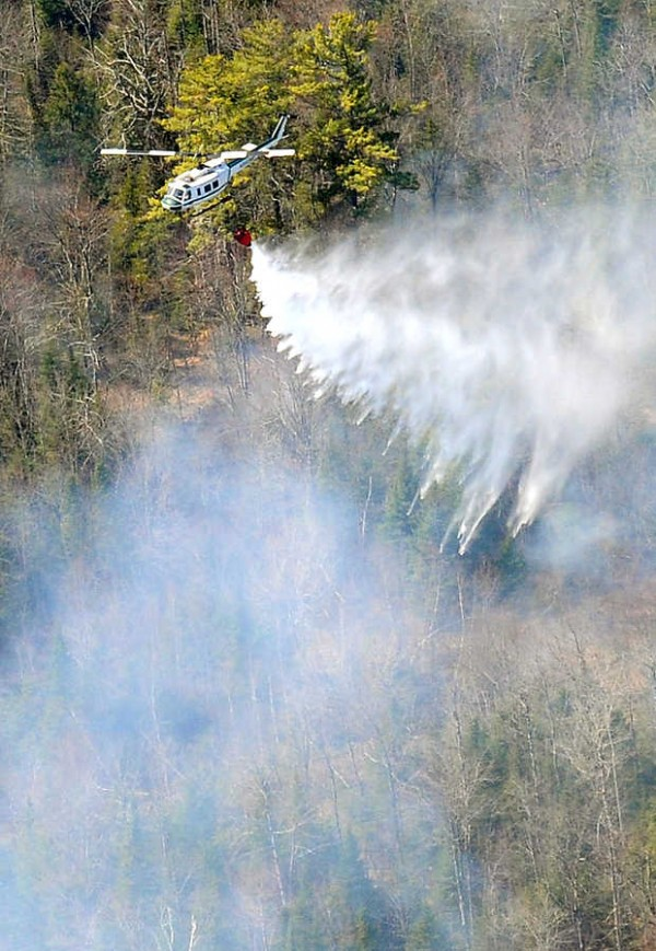 A helicopter from the State of Maine Warden Service drops water from nearby No Name Pond on a fast moving brush fire along Central Maine Power lines off of College Road in Lewiston Tuesday afternoon.