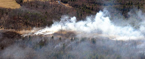 Firefighters from area departments work on a fast-moving brush fire along the power lines off of College Road in Lewiston Tuesday afternoon.