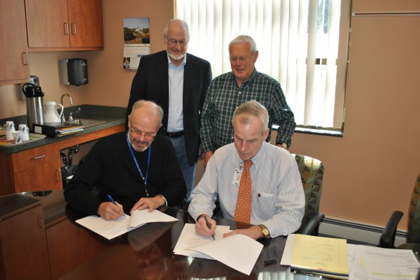 (l to r) DECH CEO Doug Jones and CRH CEO Mike Lally sign collaboration agreement as DECH Board member James Thompson and CRH Board Chair Everett Libby witness the signing.