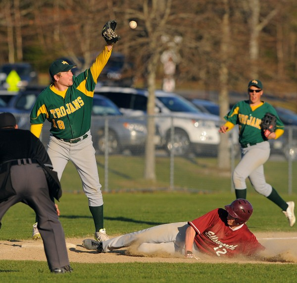 Ellsworth's Steven Mahon (right) slides to third base beating the throw to MDI's Ben Walls during the game in Ellsworth Tuesday.