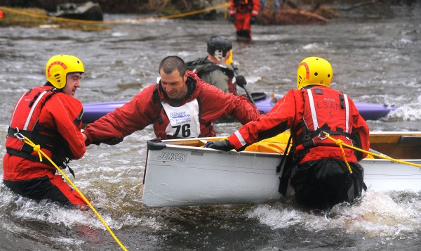 Chris Dalton of Bangor (center) is assisted by rescuers after his canoe tipped over at Six Mile Falls during the 2013 Kenduskeag Stream Canoe Race.